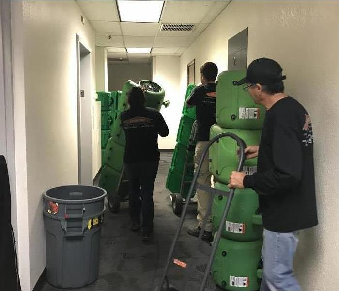 Three technicians introducing air movers in a building for drying purposes after water damage