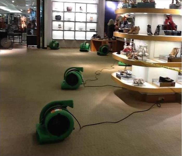 Air movers placed on carpet floor of a store